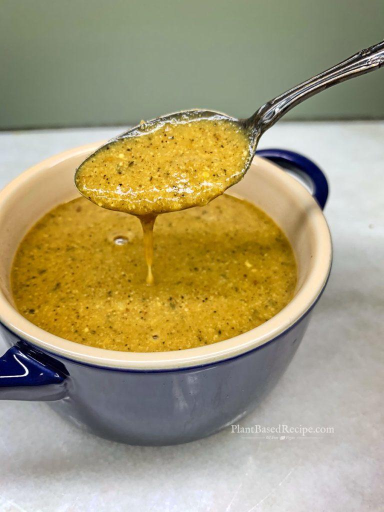 vegan simple miso gravy recipe - spooning gravy from a bowl