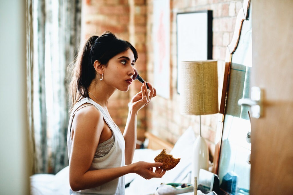 Photo features a woman applying cosmetics in front of a mirror.