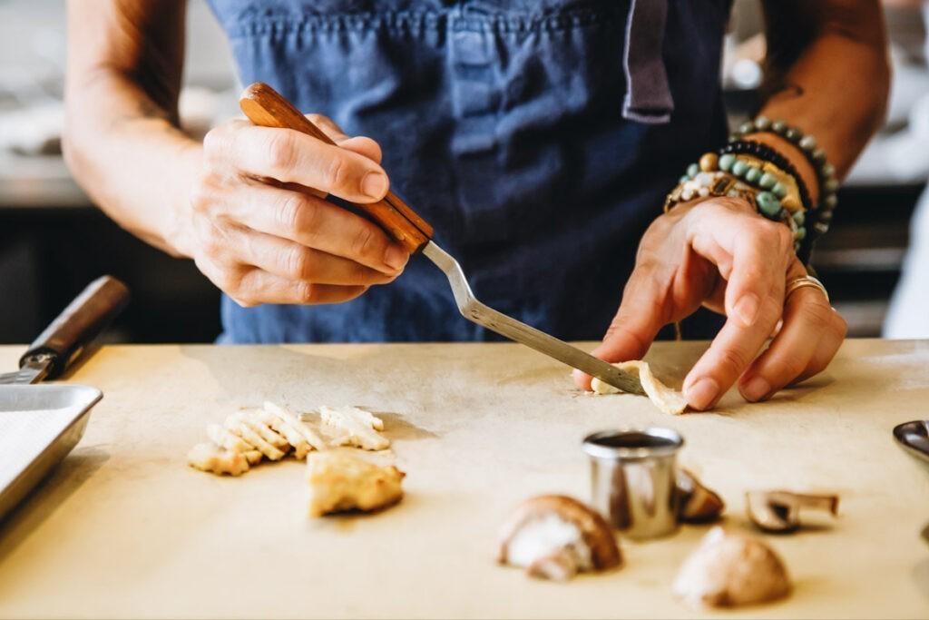 Photo shows Dominique Crenn preparing Upside Foods' cultured meat to serve in her restaurant, Atelier Crenn.