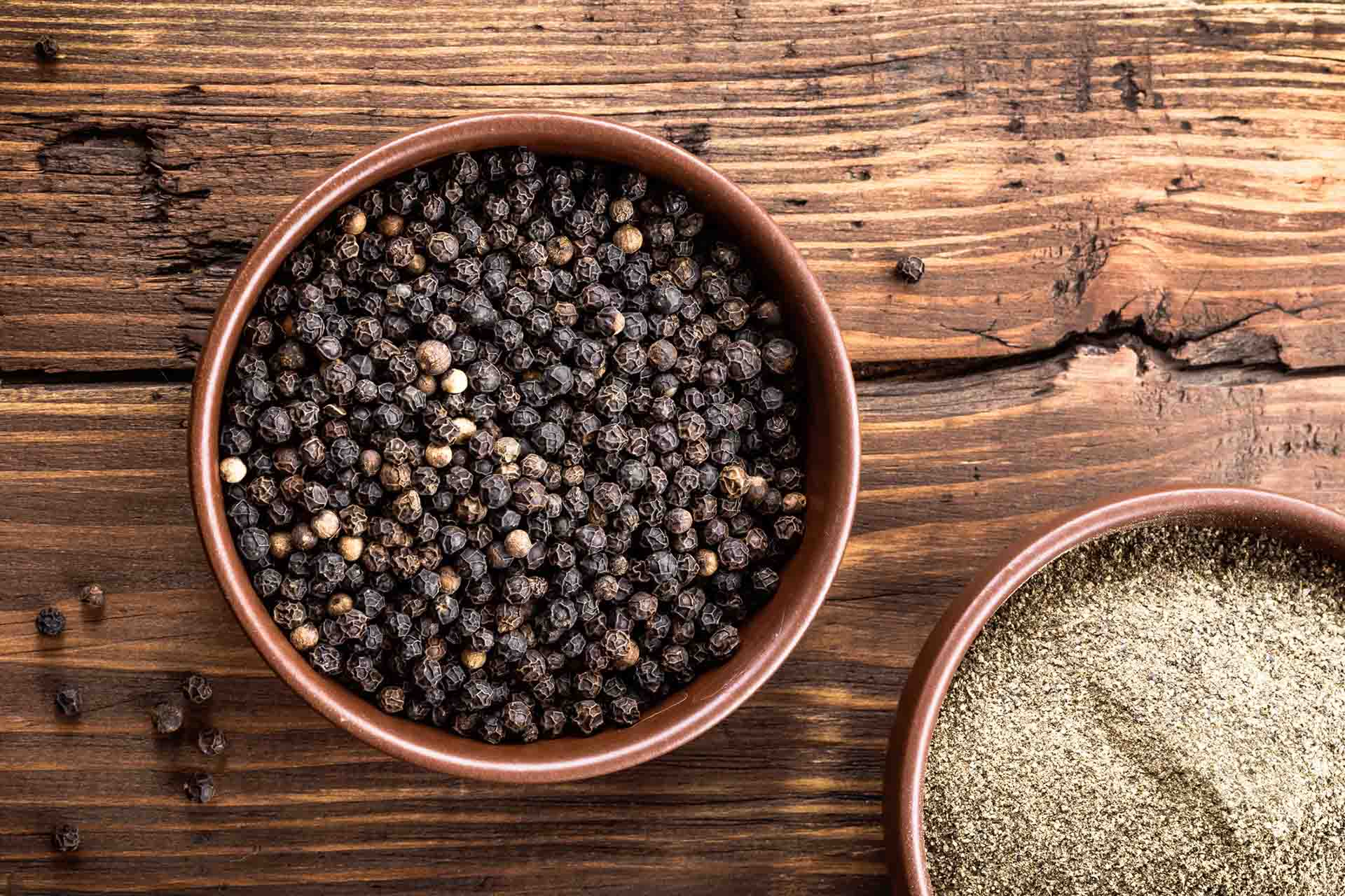 Bowl of black peppercorns sitting on a wooden table.