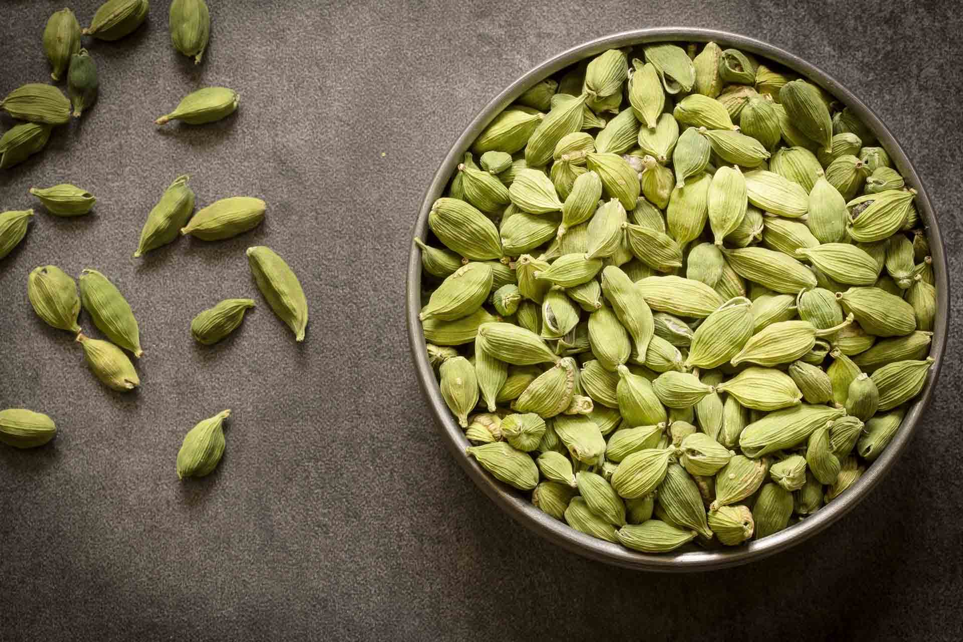 Green cardamom pods in steel bowl with wooden background.