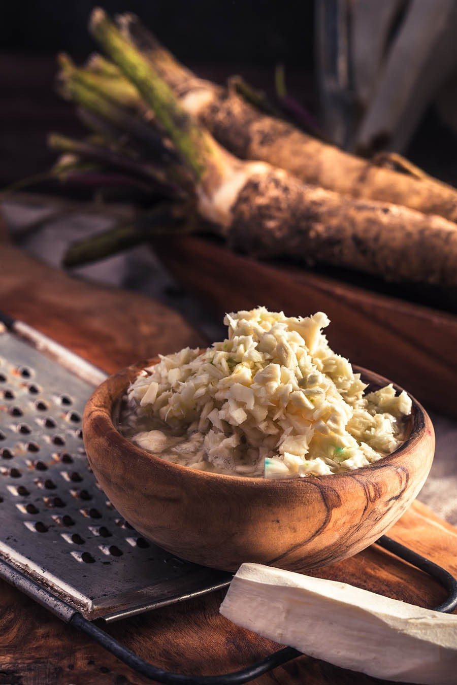 Wooden bowl of coarsely grated horseradish on table