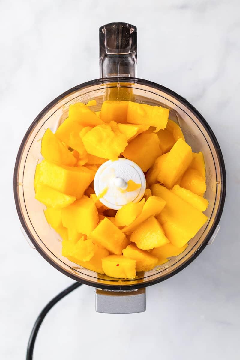 food processor full of mango chunks for vegan mango ice cream