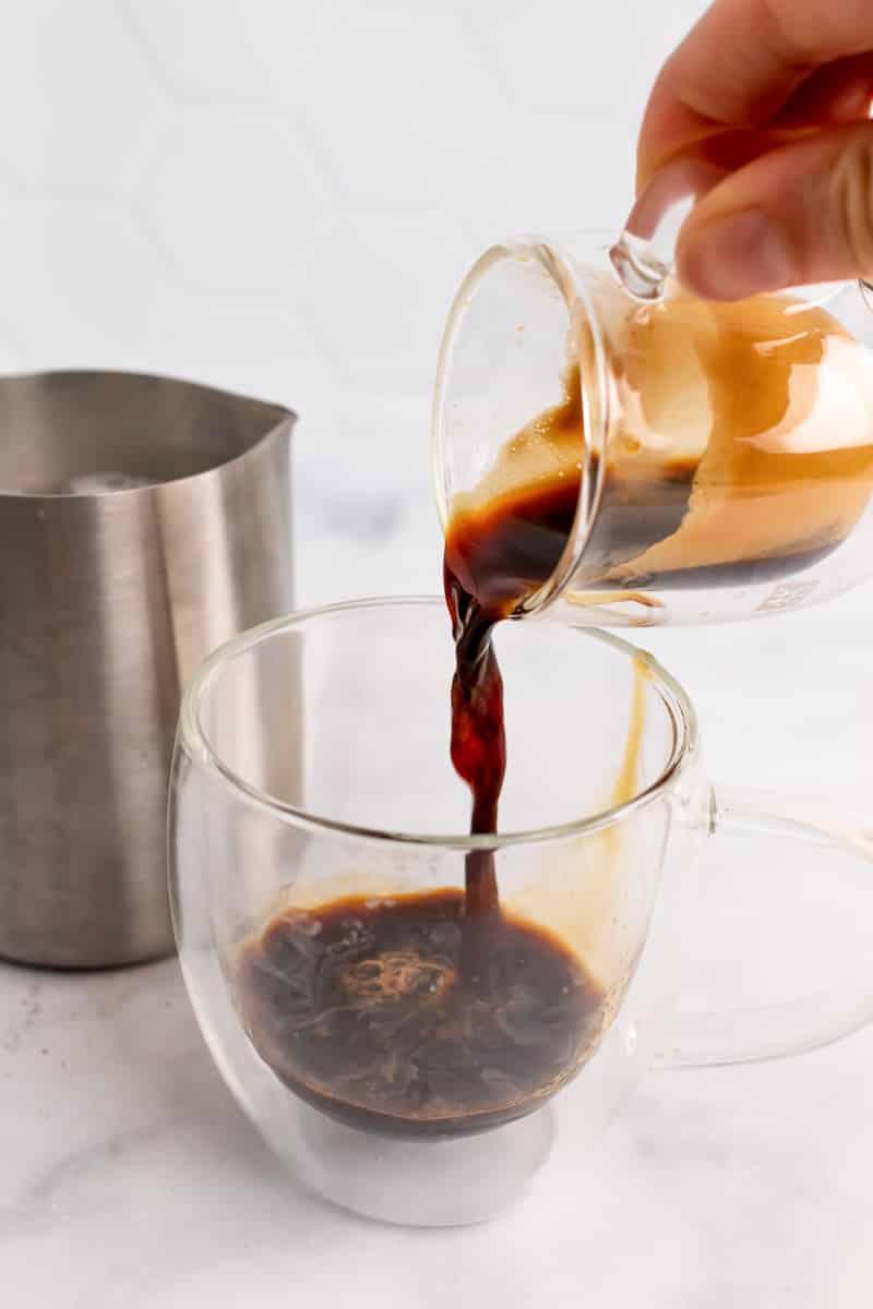 pouring espresso into glass for oat milk latte