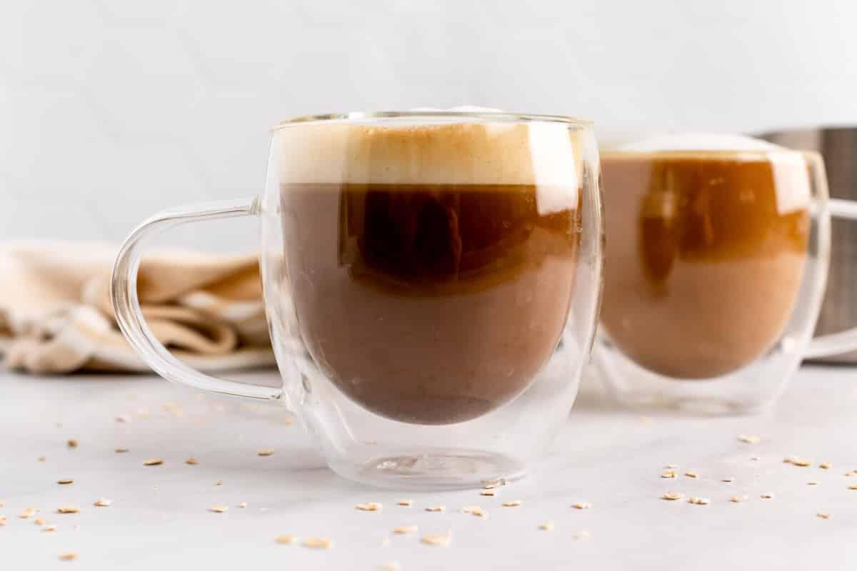 side view two cups of oat milk latte