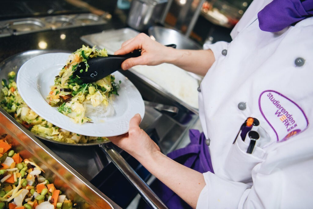 Photo shows cook Nicole Graf serving a vegan dish of glass noodles and Chinese cabbage at Berlin's Technical University, now almost entirely meat-free.