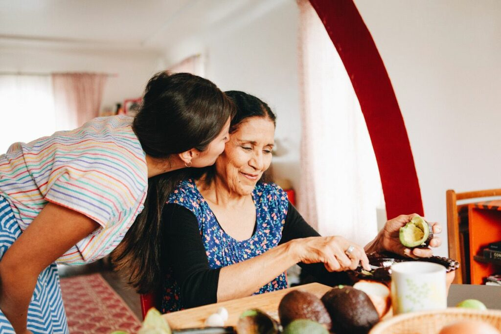 A Latin American granddaughter kisses her grandmother on the cheek.