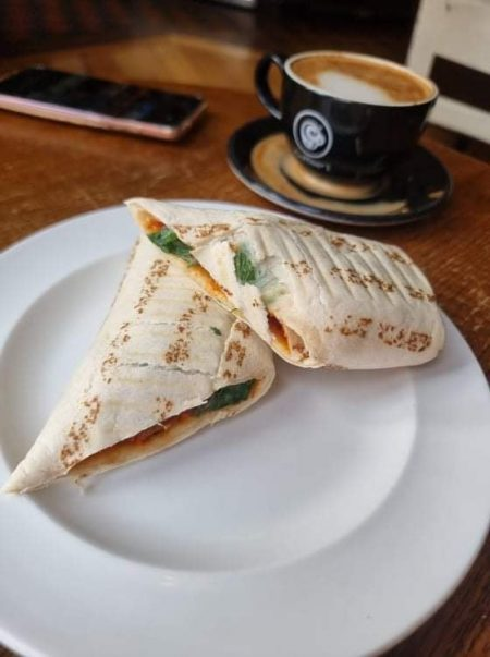 vegan meatball wrap next to a cup of coffee