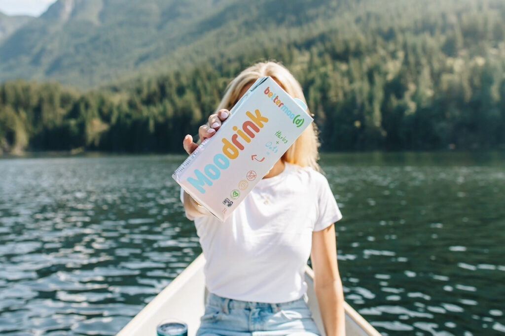 """Photo shows a blond woman sat in a boat on a scenic lake holding a cartoon of Bettermood's """"Moo Drink"""" plant-based milk up in front of her face."""