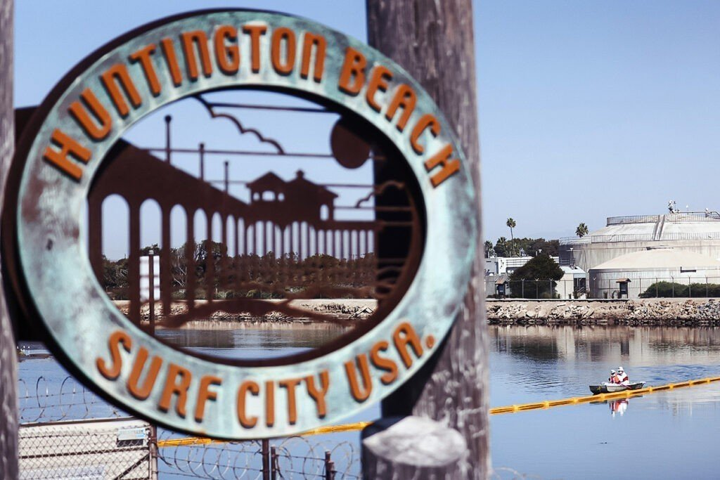"""Photo shows a sign that reads: """"Huntington Beach Surf City USA,"""" with an inlet and boat in the background."""