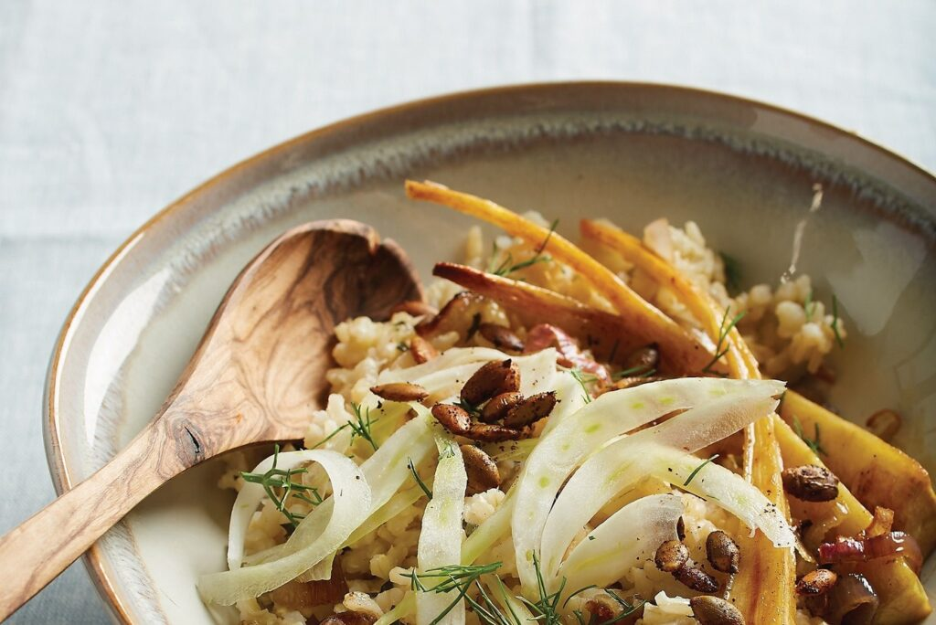 Photo of a brown rice bowl with maple-roasted parsnips, shallots, and spicy pumpkin seeds