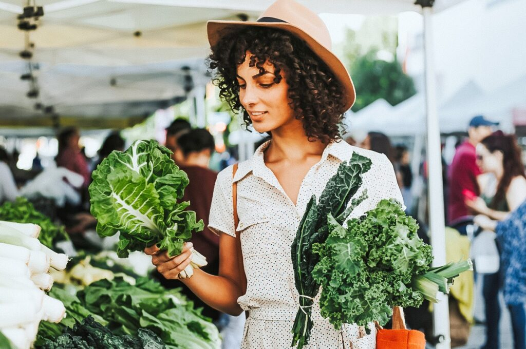 Photo shows a women shopping for fresh produce at an outdoor market and is holding two different varieties of leafy greens.