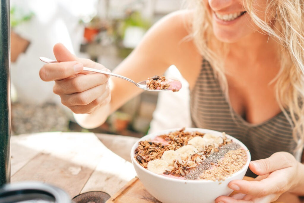 Photo shows someone eating a nutritious yoghurt, granola, and seed bowl.